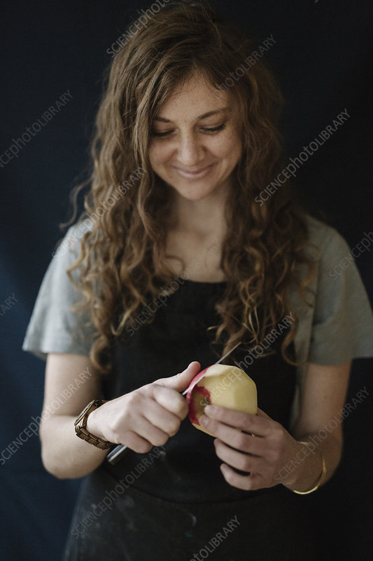 Woman peeling an apple with a knife