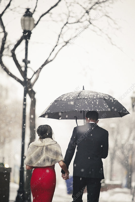 Couple in evening dress in a city in snow