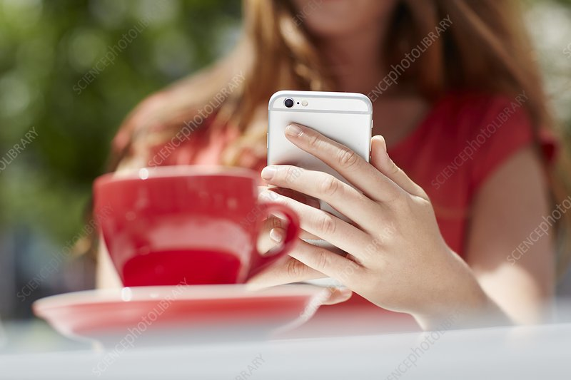 Woman using smartphone with coffee