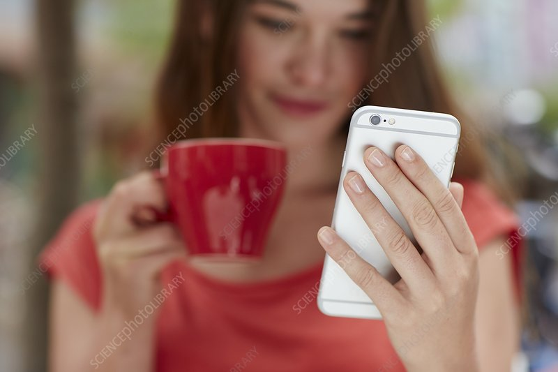 Woman using smartphone drinking coffee