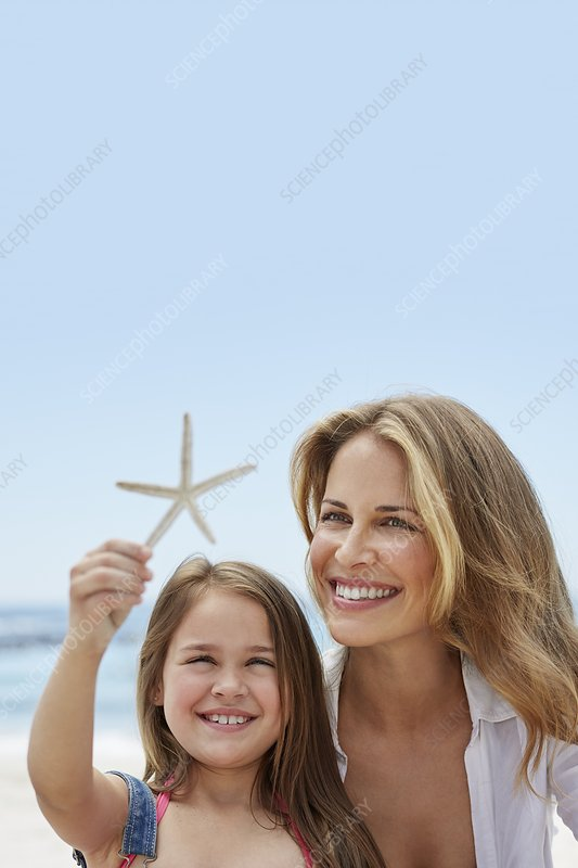 Mother with daughter holding a starfish