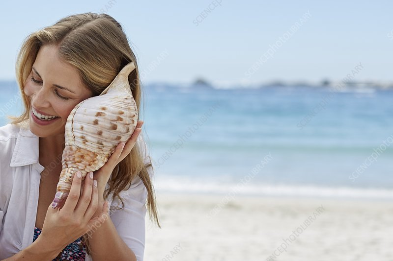 Woman listening to a seashell
