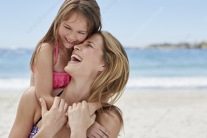 Mother carrying daughter on back