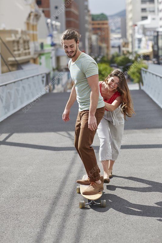 Man skateboarding with woman pushing