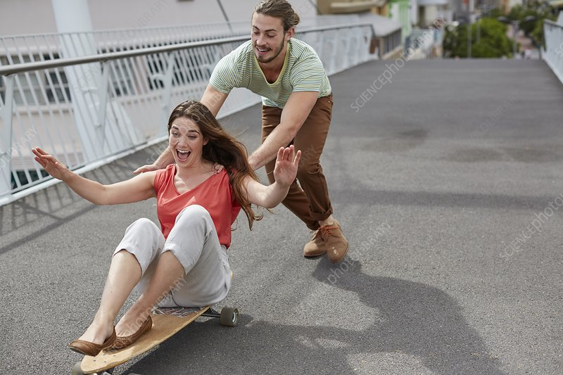 Woman on skateboard, man pushing