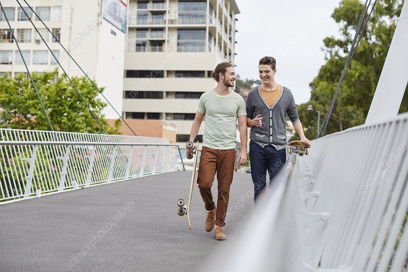 Two young men walking with skateboards