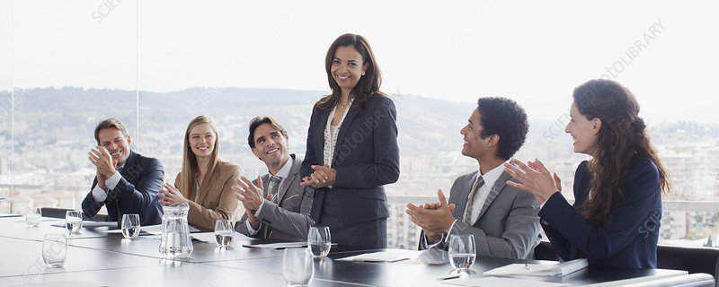 Co-workers clapping for businesswoman