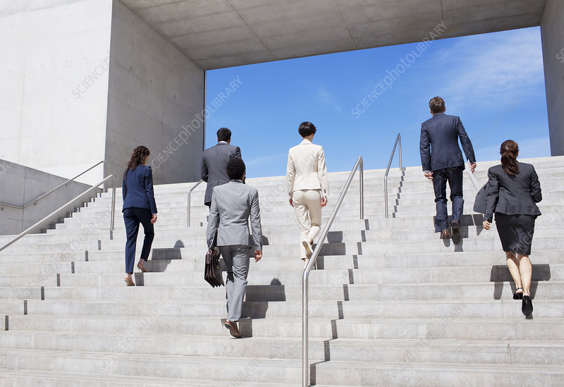 Business people ascending urban stairs