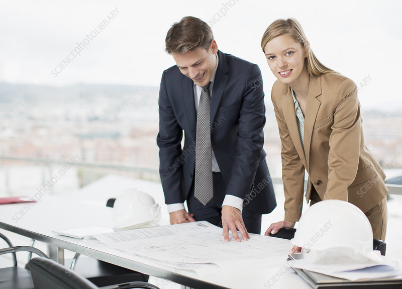 Architects reviewing blueprints at desk