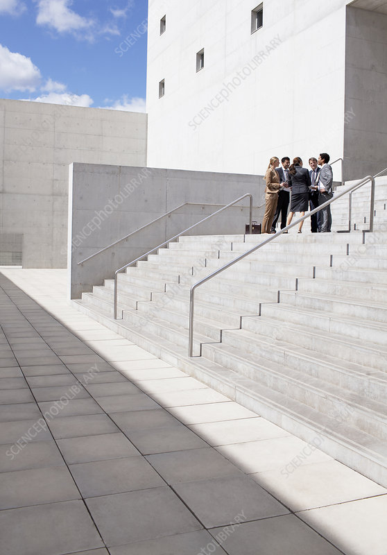 Business people meeting on urban stairs