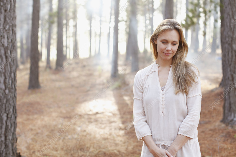 Portrait of serene woman in sunny woods