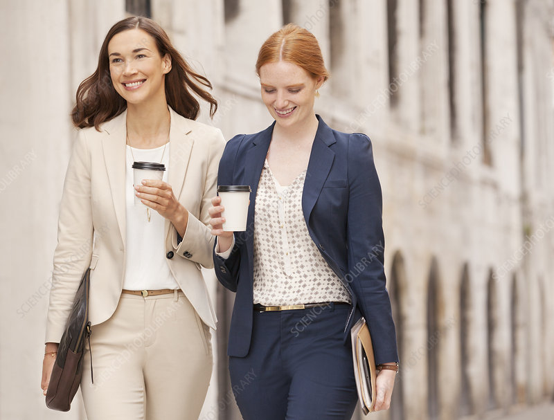 Smiling businesswomen walking