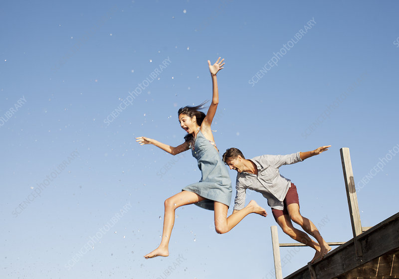 Exuberant couple jumping off dock