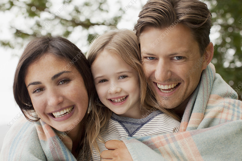 Smiling family wrapped in blanket