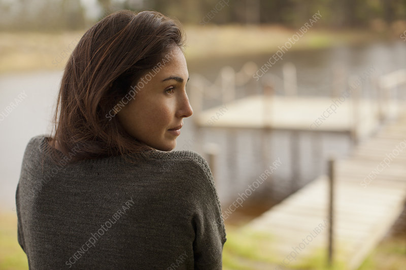 Pensive woman at lakeside