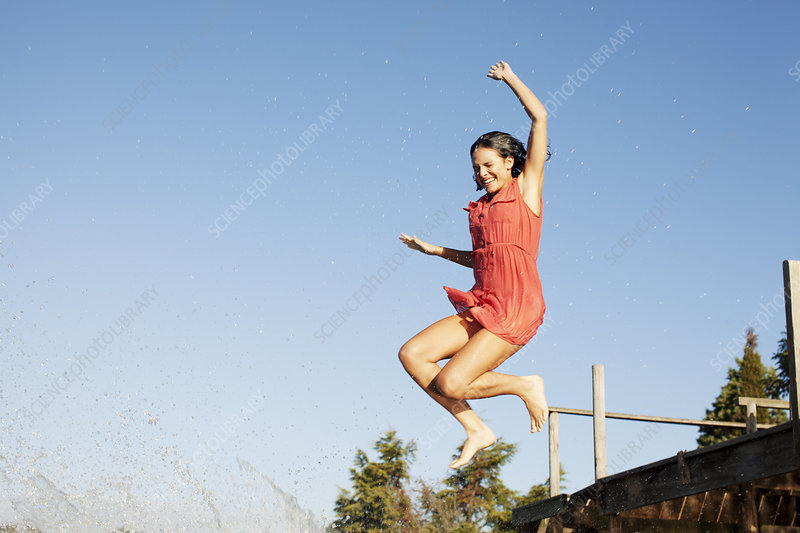 Smiling woman jumping off dock
