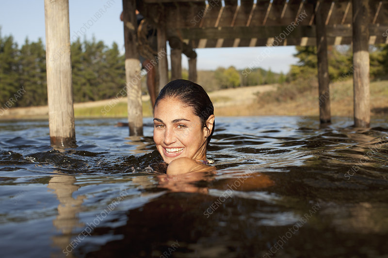 Smiling woman swimming in lake