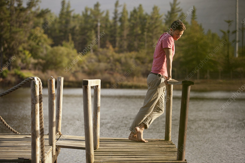 Serene man standing at railing of dock