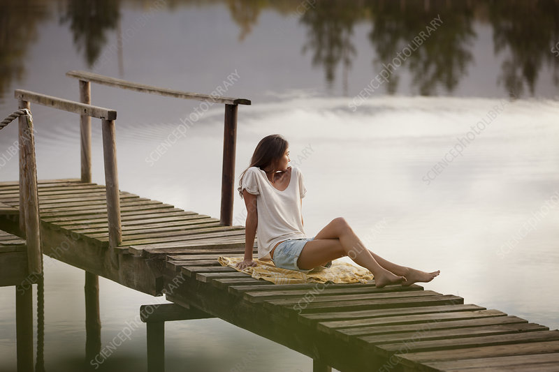 Woman sitting on dock over lake