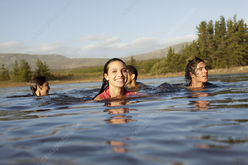 Smiling friends swimming in lake