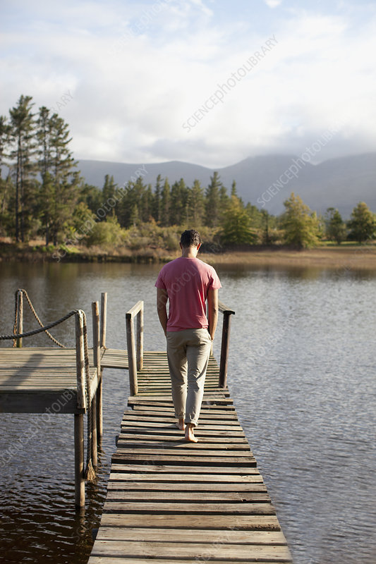Man walking along dock over lake