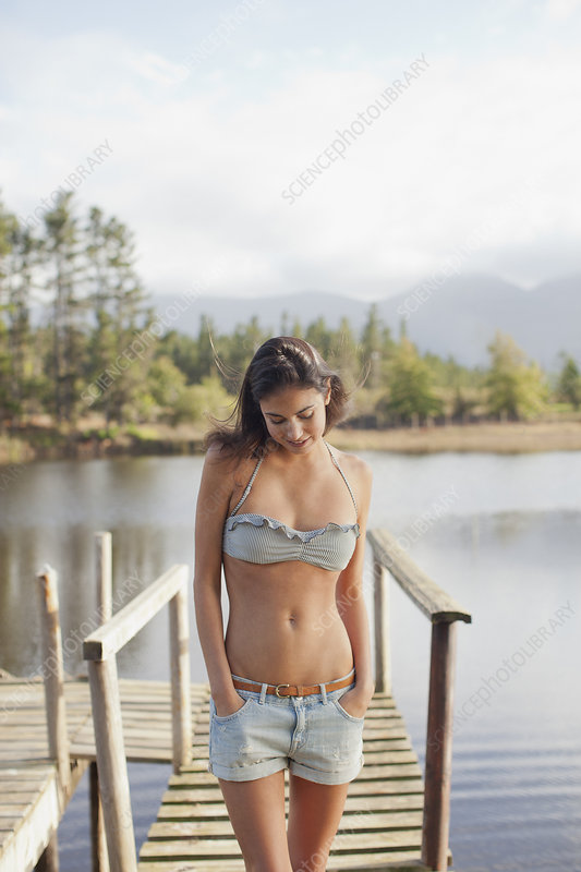 Woman looking down with hands in pockets