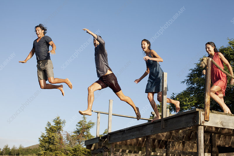 Enthusiastic friends jumping off dock