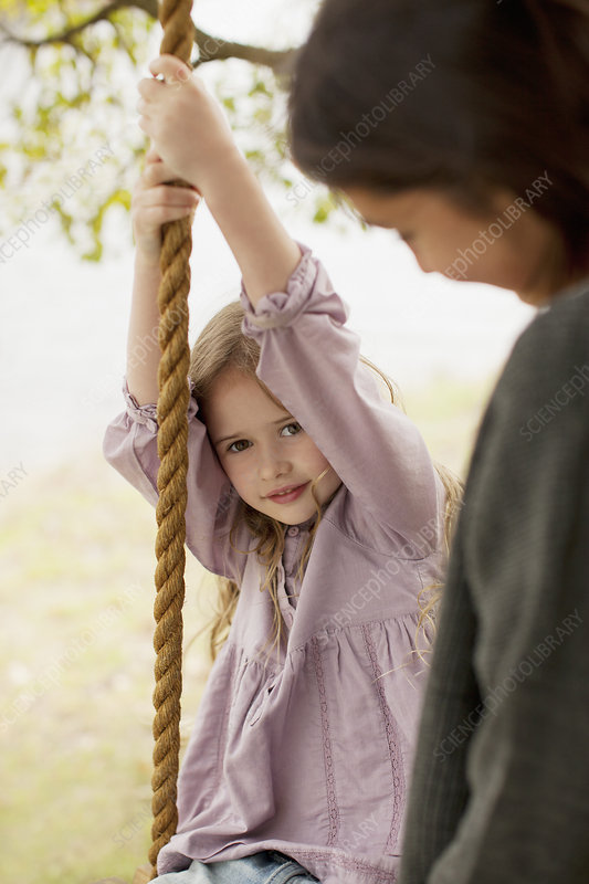 Portrait of girl on swing with mother