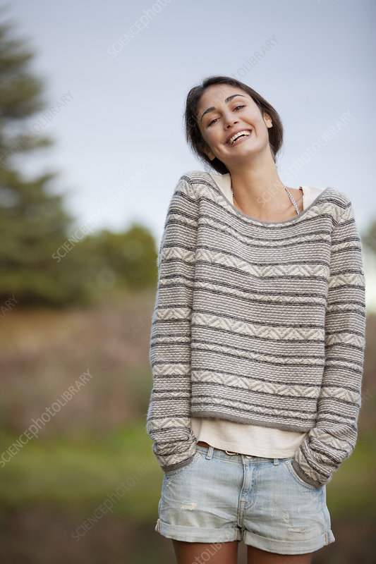 Smiling woman with hands in short pockets