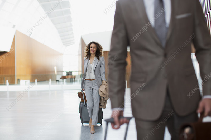 Smiling businesswoman pulling suitcase