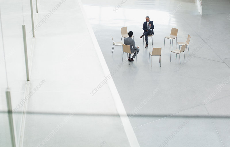 Businessmen meeting at circle of chairs