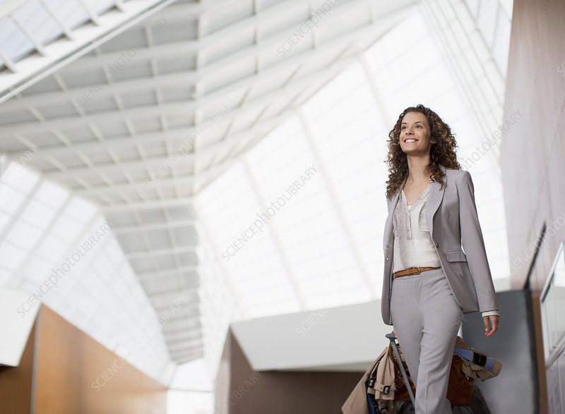 Smiling businesswoman carrying suitcase