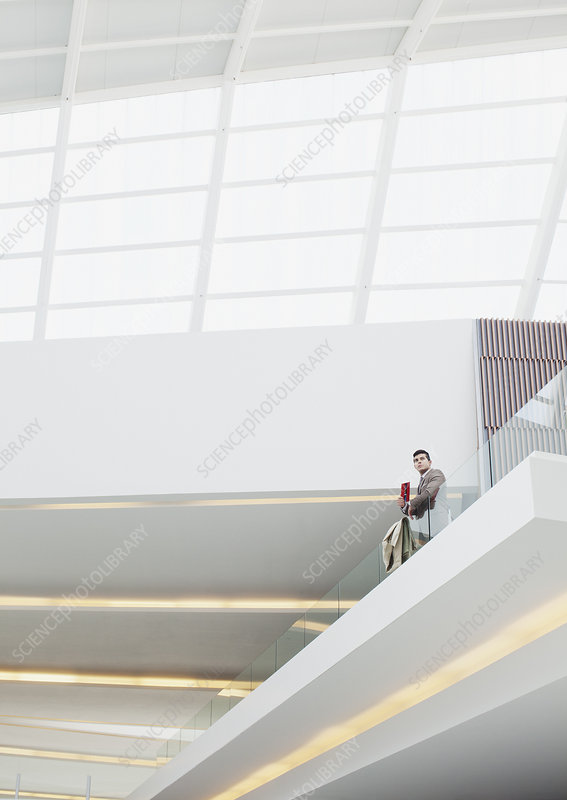 Businessman standing at balcony railing