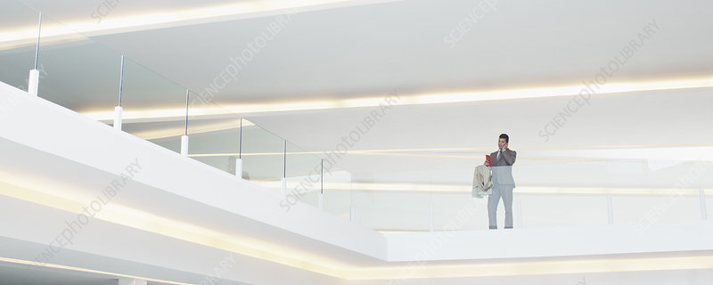 Businessman at glass balcony railing