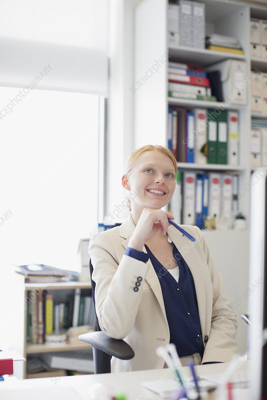 Smiling woman looking up in office