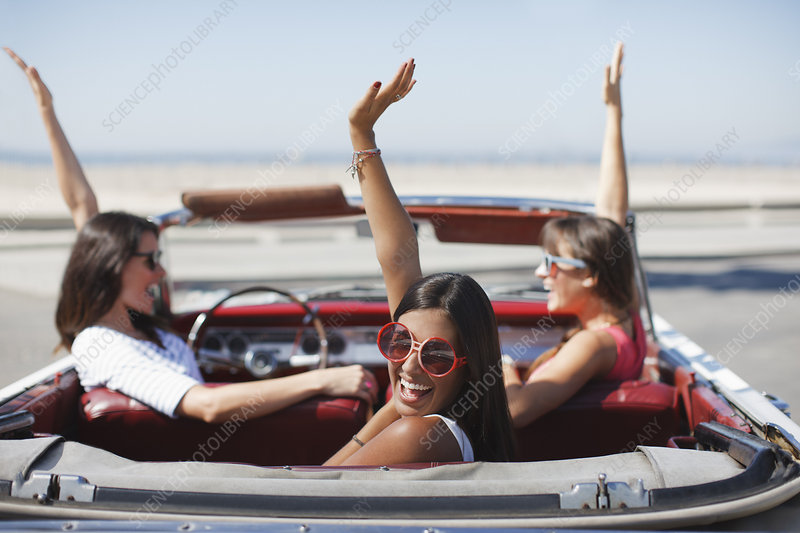 Women cheering in convertible
