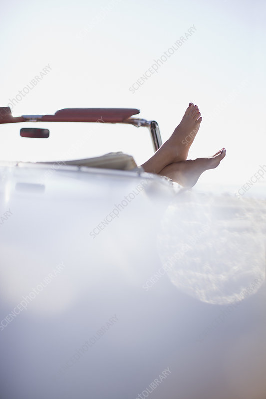 Woman's feet resting on convertible