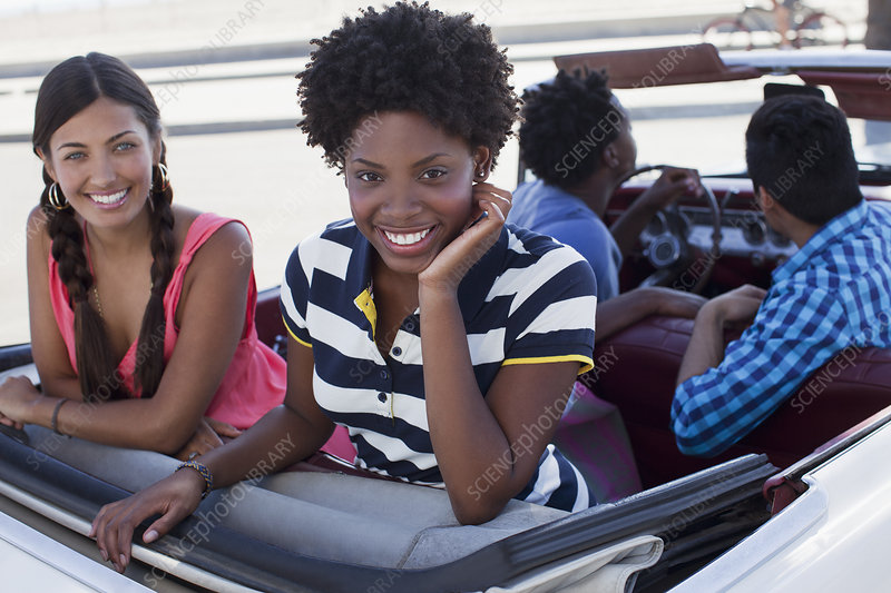 Smiling women sitting in convertible