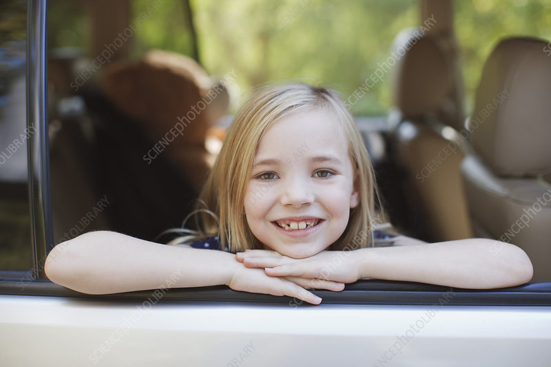 Smiling girl leaning out car window