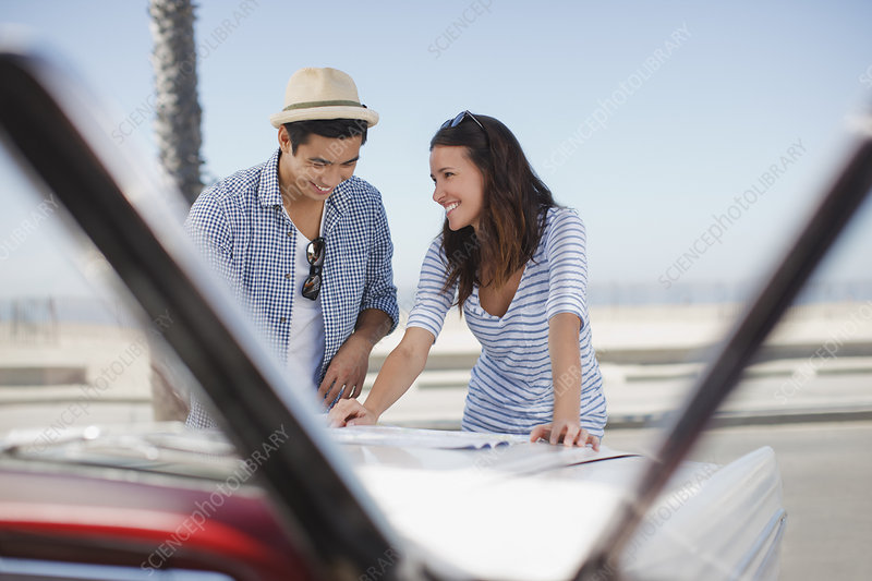 Smiling couple reading road map