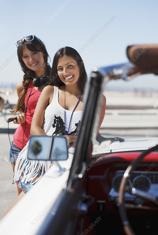 Smiling women standing by convertible
