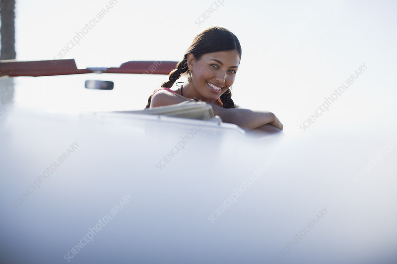 Smiling woman leaning out of convertible