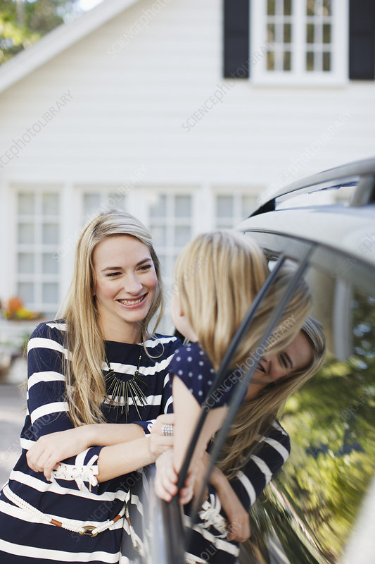 Mother talking to daughter in car window