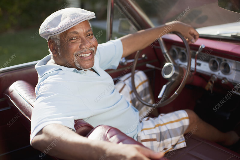 Smiling older man driving convertible