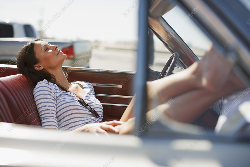 Smiling woman relaxing in convertible