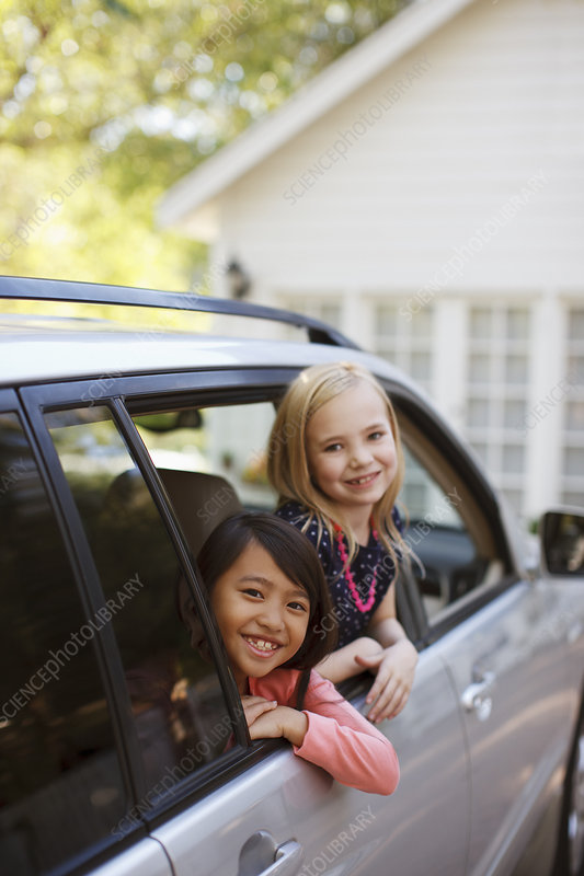 Girls smiling out car window