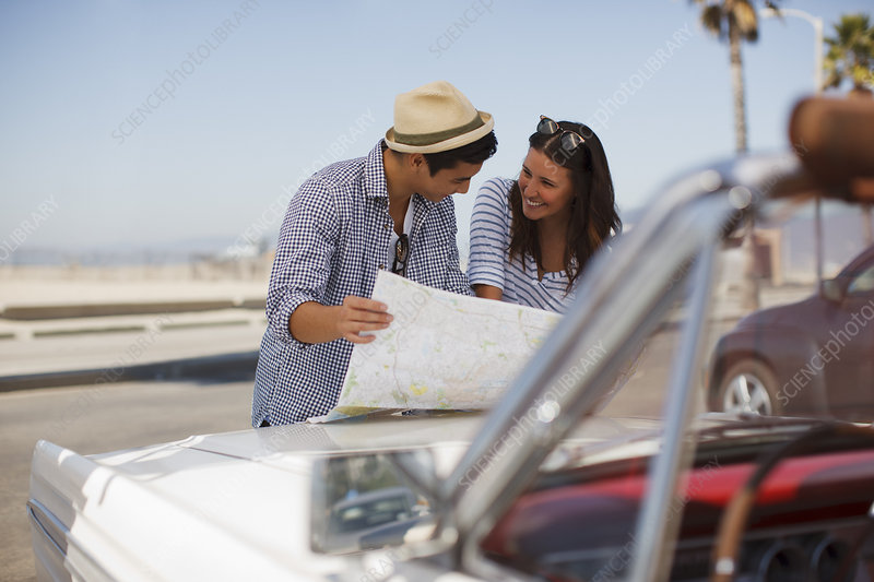 Couple reading road map on convertible