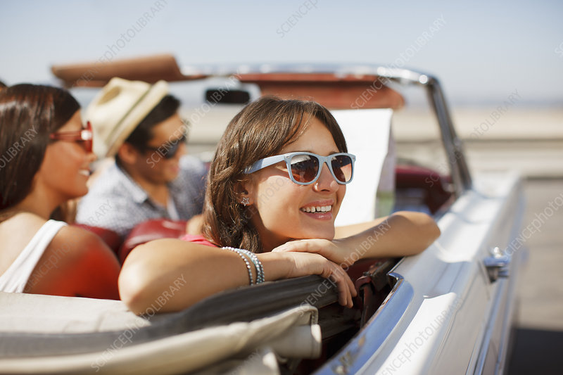 Smiling woman leaning out convertible