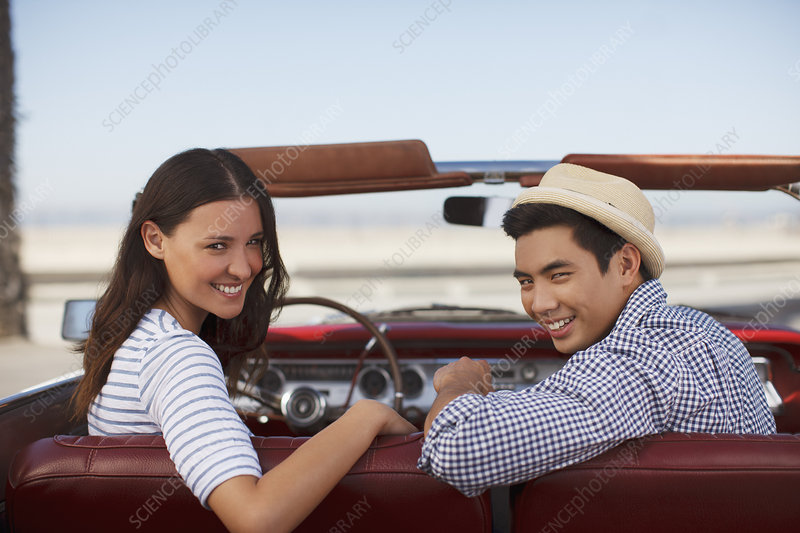 Smiling couple sitting in convertible