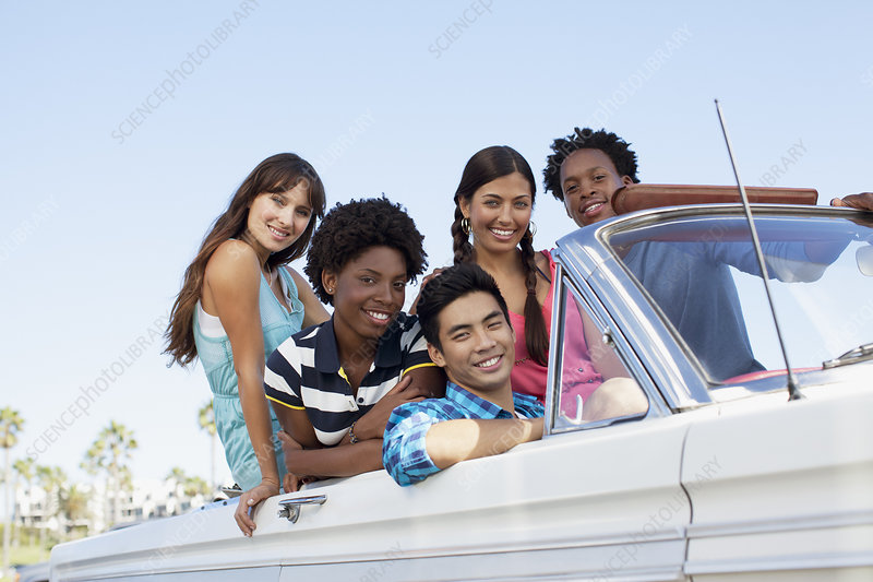 Smiling friends sitting in convertible